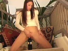Hot chick stuffing wine bottle in her cunt