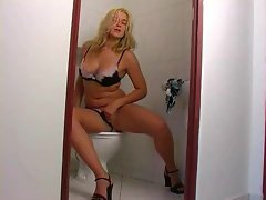 She rubs her fabulous clit on the toilet