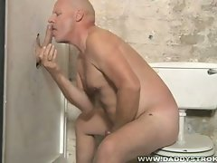 Older mature gay sucking and stroking long cock at gloryhole