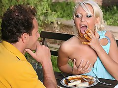 A blonde girl and a guy are eating at a picinic table. The girl...