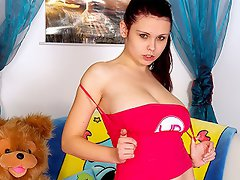 A busty looking teenage girl is sitting on the bed doing her...