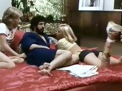 A guy is laying on the bed, taking to two young, blonde girls. The...