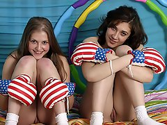 Two teenage girls are frloicking about on a mattress. While they are...