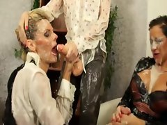 Classy clothed lesbians get covered in cum after sucking plastic cock