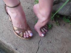 Flexes feet in sandals