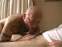 Two tatooed gay making love on the bed