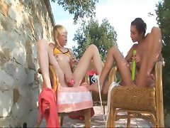 Lesbian teens outside in chairs are using toys on their pussies