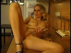 Horny blonde masturbates in kitchen