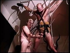 Chains and straps suspend one gay and the other gay is the master