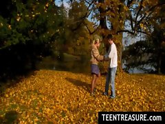Teen couple kissing in park on beautiful autumn day