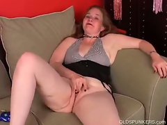 Mature redhead lubes up a dildo to toy her own pussy