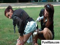 Two crazy babes are outside by the road rubbing cream on each other