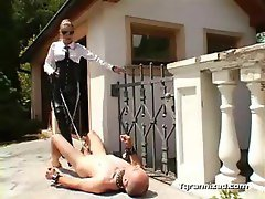 Man tortured by dominatrix outdoor
