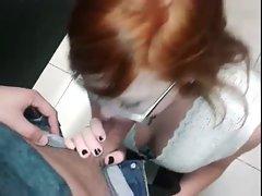 Redhead young woman fellatio dick in public bathroom