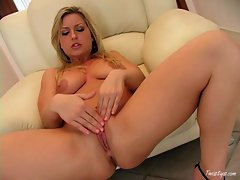 Solo babe Avy Scott massaging her clit and pussy with her fingers on the couch