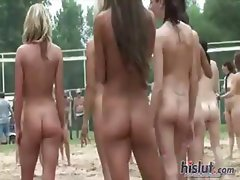 Naked girls are outside posing before they play a game at a park