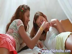 Two skinny lesbian teens are in bed kissing and licking titties