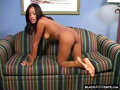 Ebony tramp with a slender figure displays her goodies on the couch