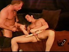 CBT hot young muscle stud's ball sack clamped off from his cock between two pieces of clamped wood.