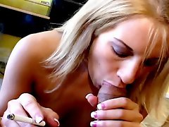 Beautiful blonde seductress Desire Moore smoking with lust and...