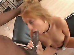 Slutty redhead Desire Moore lays back on a leather lounge chair while...