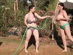 Busty beauties playing with hose outdoors
