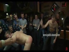 Stud is tied up in a bar and has his balls and torso covered in nipple clamps
