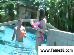 Brunette teen goes in the pool with her man and shows tits