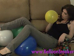 Teen blowing up balloons