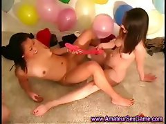 Lesbian amateurs play with double dildo at party
