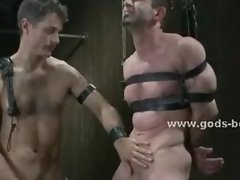 Gay master tortures bound slave with wax and bondage clips in nas