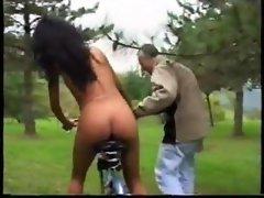 She rides a dildo bike in the grass
