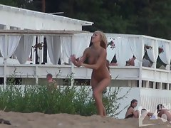 Luxury naked blonde playing volleyball at the nudist beach