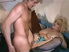 A chubby blonde woman is crouched on her knees on a bed, getting...