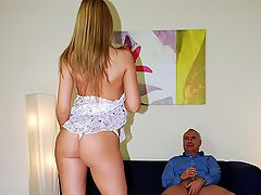 A guy is sitting on a couch talking to the camera. A young girl sits...