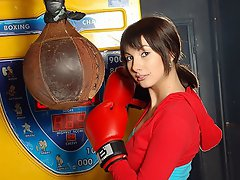 A young girl is posing in front of the camera wearing boxing gloves....