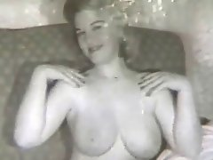 A blonde girl with large tits is sitting on a sofa, showing her naked...