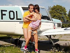 A young girl is standing next to a small airplane. A guy comes up to...