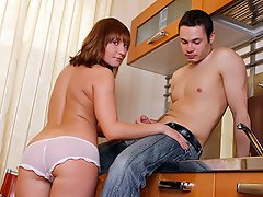 A young couple is in the kitchen. She is topless and he plays with...