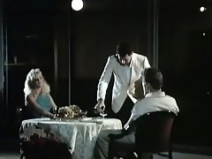 A couple is sitting at a restaurant table where a waiter is serving...