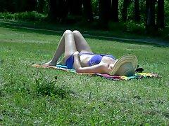 Attractive mom sunbathing in public park