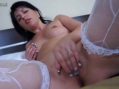 Attractive Mommy in luscious lingerie playing on bed